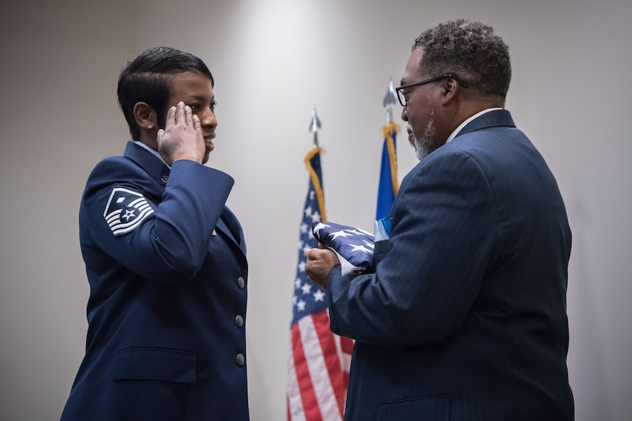 Master Sgt. Robin Robertson, 81st Training Wing first sergeant, presents a retirement flag Gary Wallace, 53rd Weather Reconnaissance Squadron aviation resources management technician, during his retirement ceremony Feb. 2, 2018 at Keesler Air Force Base, Mississippi. (U.S. Air Force photo by Staff Sgt. Heather Heiney)