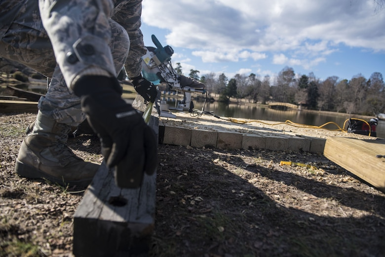U.S. Air Force 1st Lt. Alvin Yip, 20th Civil Engineer Squadron deputy officer in charge of requirements and optimization, measures a piece of wood in front of Memorial Lake at Shaw Air Force Base, S.C., Feb. 5, 2018.