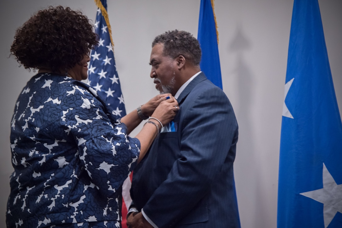 Yolanda Wallace places a retirement pin on the lapel of her husband, Gary Wallace, 53rd Weather Reconnaissance Squadron aviation resources management technician, during his retirement ceremony Feb. 2, 2018 at Keesler Air Force Base, Mississippi. (U.S. Air Force photo by Staff Sgt. Heather Heiney)