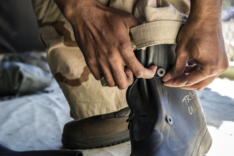 Tech Sgt. Kendrick Butler, 23d Maintenance Squadron assistant NCO in charge of aircraft metals technology, tightens his boots, Feb. 1, 2018, at Moody Air Force Base, Ga. Airmen participated in a chemical, biological, radiological and nuclear defense (CBRNE) class to better prepare them to combat enemy attacks while also familiarizing them with mission-oriented protective posture (MOPP) gear. (Air Force photo by Airman Eugene Oliver)
