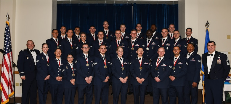 Col. Mathew Dillow, 90th Missile Wing vice commander and Chief Master Sgt. James Gray, 90th Medical Group chief enlisted manager, pose with the graduating Airman Leadership School Class 18-C students at F.E. Warren Air Force Base, Wyo., Feb. 7, 2018. Enlisted Airmen must complete this professional military education course to become supervisors of other Airmen. (U.S. Air Force photo by Airman 1st Class Braydon Williams)