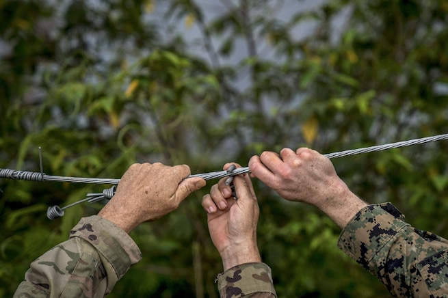 The hands of a soldier and a Marine fix a wire on a fence.