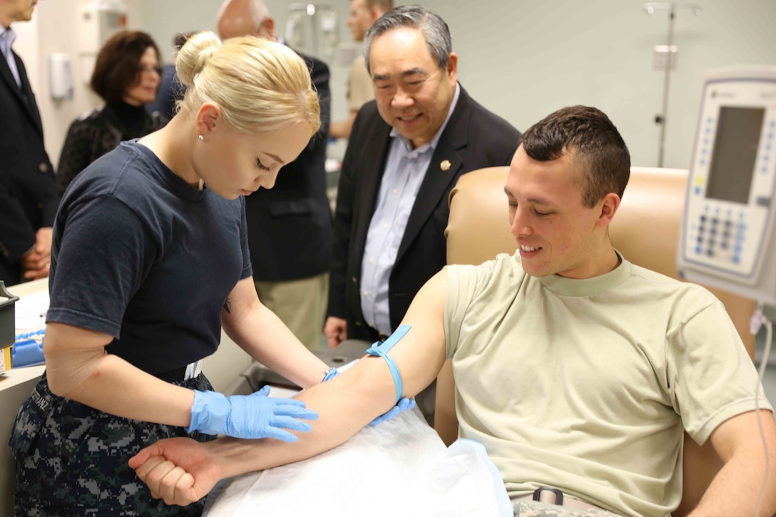 Dr. Kenneth Moritsugu, center, a member of the Uniformed Services University of the Health Sciences board of regents, watches students in the Medical Education and Training Campus medical laboratory technologist course practice blood draws.