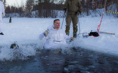 Norwegian Maj.Gen. Odin Johannessen, the chief of Norwegian Army, participates in an ice-breaking drill alongside Maj.Gen. Russell A.C. Sanborn, the commander of Marine Corps Forces Europe and Africa, in Bardufoss, Norway, Jan. 31, 2018. Sanborn participated in this training evolution to experience the training the Marines have endured throughout their time in Norway. The drill is a cornerstone of advanced cold-weather training, intended to teach a service member the immediate steps to take when falling in ice.  (U.S. Marine Corps photo by Cpl. Careaf L. Henson/Released)