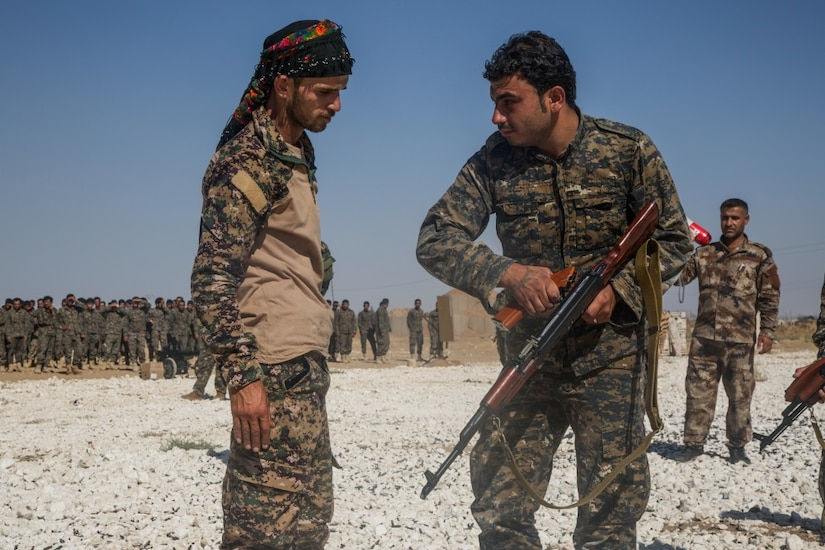 An instructor with the Syrian Democratic Forces observes as a Syrian Arab trainee clears his rifle during small-arms training in northern Syria.