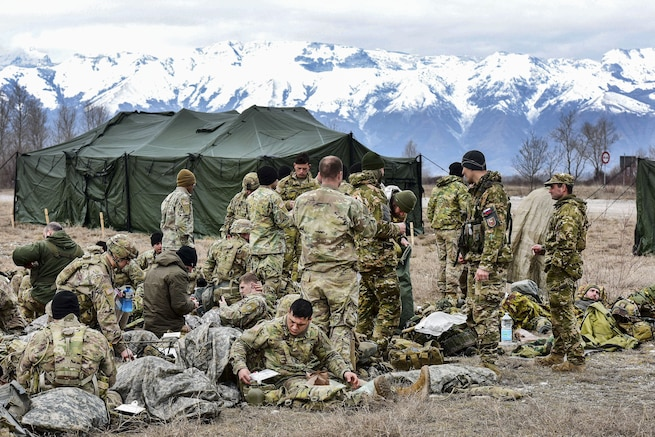 U.S., Italian and Slovenian soldiers relax outside with mountains behind them.