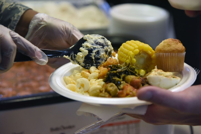 Airmen serve soul food to guests during the African American Heritage Committee soul food sampling at the Larcher Chapel Feb. 8, 2018, on Keesler Air Force Base, Mississippi. The event, held in observance of African American History Month, accepted donations to benefit scholarship funds to help local youth pay for tuition, books and other academic costs. (U.S. Air Force photo by Kemberly Groue)