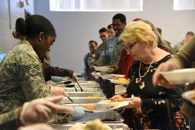 Senior Airman Arafa Simmons, 81st Operations Support Flight air traffic controller, serves collard greens to Ruthie Atchley, 81st Communications Squadron base records manager, during the African American Heritage Committee soul food sampling at the Larcher Chapel Feb. 8, 2018, on Keesler Air Force Base, Mississippi. The event, held in observance of African American History Month, accepted donations to benefit scholarship funds to help local youth pay for tuition, books and other academic costs. (U.S. Air Force photo by Kemberly Groue)