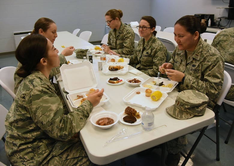 Airmen eat soul food during the African American Heritage Committee soul food sampling at the Larcher Chapel Feb. 8, 2018, on Keesler Air Force Base, Mississippi. The event, held in observance of African American History Month, accepted donations to benefit scholarship funds to help local youth pay for tuition, books and other academic costs. (U.S. Air Force photo by Kemberly Groue)