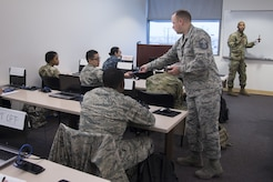 Master Sgt. Robert George, Medical Education & Training Campus pharmacy training senior enlisted leader, hands out calculators to students prior to an examination at Joint Base San Antonio-Fort Sam Houston, Feb. 5, 2018. The Department of Defense's pharmacy technician program prepares students to perform both inpatient and outpatient pharmacy operations in both traditional and non-traditional pharmacy practices. (U.S. Air Force photo by Sean M. Worrell)