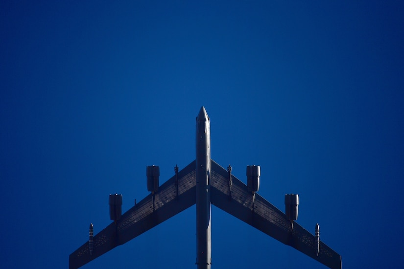 A B-52 flies in a deep blue sky.