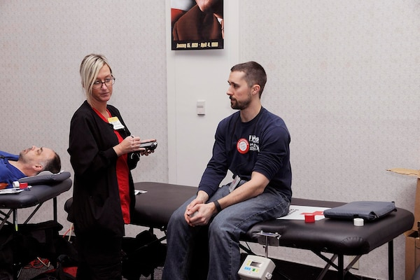 A Red Cross worker assists a donor at the Feb. 7 blood drive at the Hart-Dole-Inouye Federal Center.