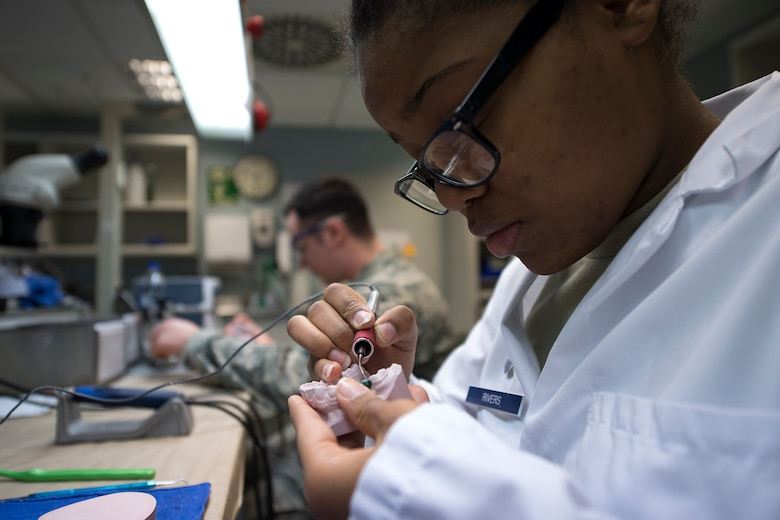 U.S. Air Force Airman 1st Class Jada Rivers, 86th Dental Squadron dental laboratory technician, fabricates a tooth for an implant at the dental clinic on Ramstein Air Base, Germany, Feb. 8, 2018. The base dental laboratory specializes in making dental appliances to include dentures, crowns, and mouth guards. (U.S. Air Force photo by Senior Airman Devin Boyer)