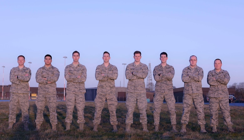 Weather forecasters from the 100th Operations Support Squadron's weather flight pose for a photo near the runway at RAF Mildenhall, England, Feb. 1, 2018. The weather flight provides accurate forecasts for the aircrews in-flight. (U.S. Air Force photo by Senior Airman Kelly O'Connor)