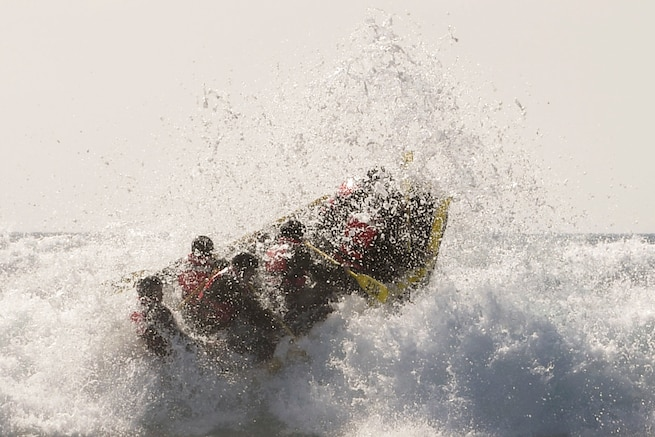Sailors in an open boat ride over explosive surf.