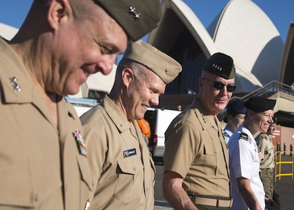 The chairman of the Joint Chiefs of staff and other Joint Staff leaders walk past the Sydney Opera House.