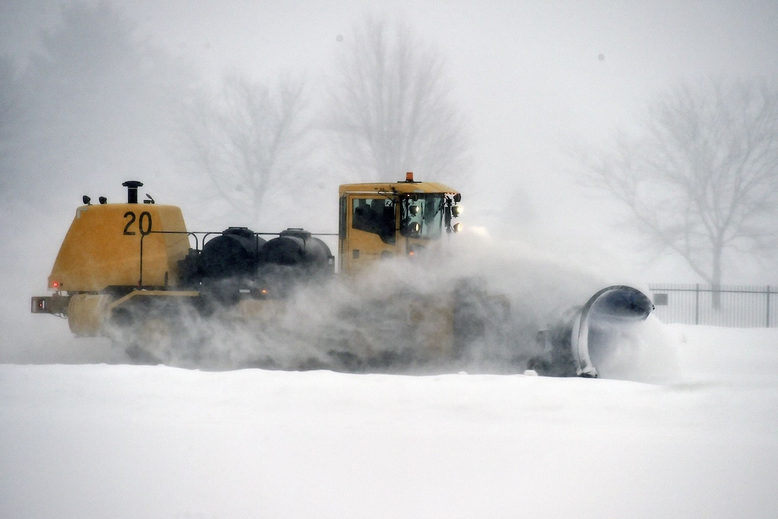 """Tom Kott, an equipment engineer with the 127th Civil Engineering Squadron, Roads and Grounds shop here, diligently clears the snow on base today, operating a heavy-duty Oshkosh snowplow meant for clearing runways, in nearly white-out conditions.  Efforts to clear base roads, parking lots, runways and airfield ramps, is necessary to allow our mission to continue unimpeded. Local weather reports estimate a total snowfall of approximately 12 inches this weekend, with the heaviest snowfall of the current storm falling between 6:00 a.m. and 11:00 a.m. today. Despite the snow accumulation and temperatures in the 20's degree Fahrenheit, Selfridge Air National Guard Base never """"closes,"""" it remains open under any prescribed contingency."""