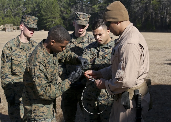 Staff Sgt. Steve Gomez watches as Lance Cpl. Darius Mason practices with detonating cord during a Demo Day, aboard Marine Corps Air Station Beaufort, Feb. 1.Gomez an EOD Technician with Marine Wing Support Detachment 31 and Mason is an administrator with Headquarters and Headquarters Squadron.