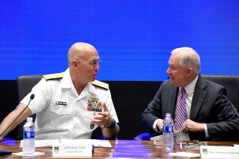 A Navy admiral and the attorney general talk while sitting behind a desk.