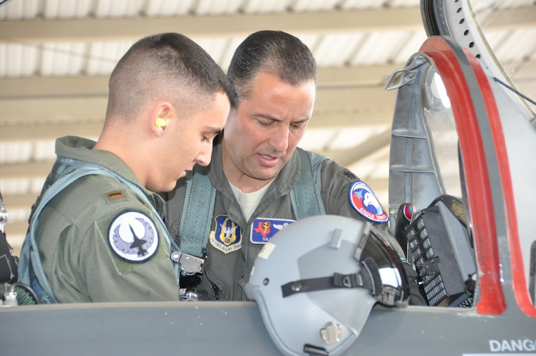 Lt. Col. Joe Mirarchi, mission commander, checks to ensure 2nd Lt. Chris Mirarchi is correctly situated in the aircraft prior to the lieutenant colonel's fini flight, and the lieutenant's first Air Force sortie. (U.S. Air Force photo by Debbie Gildea)