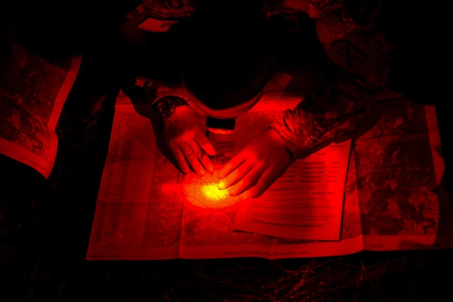 A soldier uses a headlight while crouching over a map at night, illuminating the scene in red.