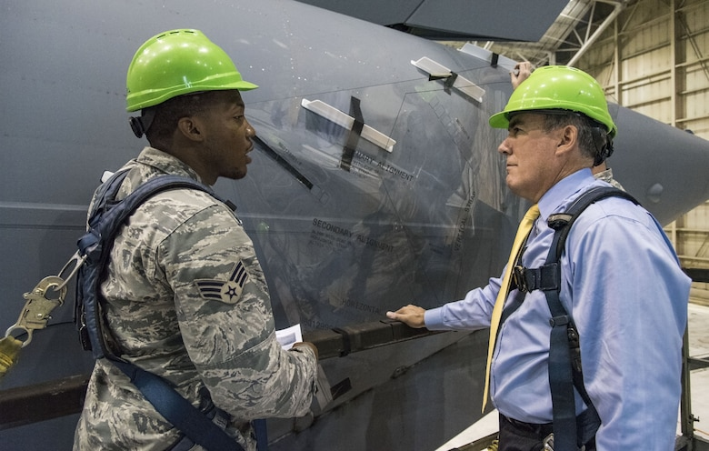 "Senior Airman Terrence Williamson, 736th Aircraft Maintenance Squadron aerospace maintenance journeyman, explains to Roberto Guerrero, Deputy Assistant Secretary of the Air Force for Operational Energy, Headquarters U.S. Air Force, Washington, D.C., how Microvanes positioned on each side at the rear of a C-17 Globemaster III fuselage using a Mylar template, Sept. 6, 2017, at Dover Air Force Base, Del. Microvanes essentially clean up the airflow in the region of the cargo door by re-energizing the air with small vortices that delay separation, smooth the flow, and reduce drag. ""The programs APTO is working on are great examples of how we can increase our combat capability through the smart use of operational energy,"" said Guerrero. (U.S. Air Force photo by Roland Balik)"