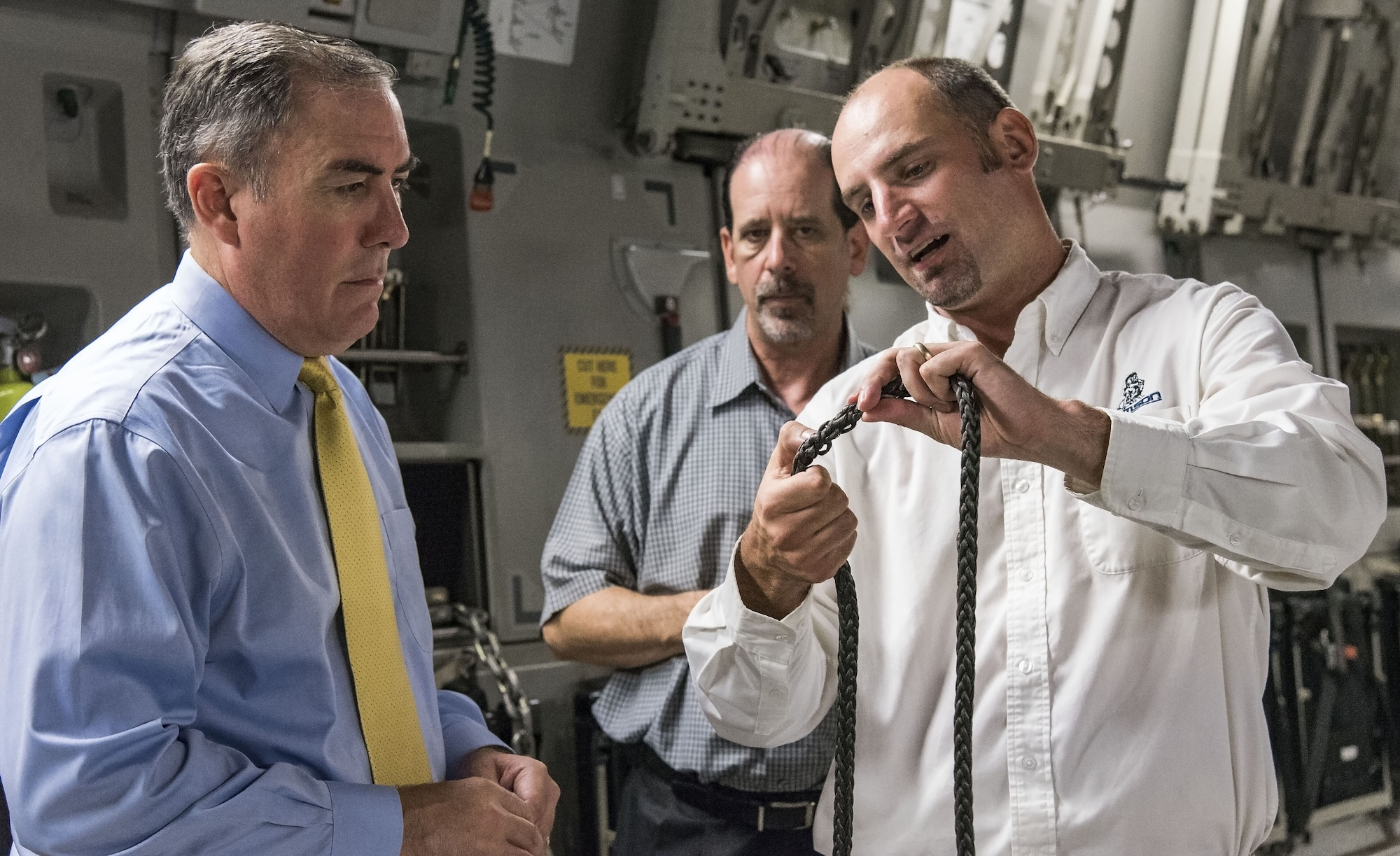 Justin Smoak, Samson Rope application engineering manager, Ferndale, Wash., right, shows Roberto Guerrero, Deputy Assistant Secretary of the Air Force for Operational Energy, Headquarters U.S. Air Force, Washington, D.C., left, and Ed Clark, AFRL aircraft programs support contractor with Concurrent Technologies Corporation, Johnstown, Pa., the weaving of the synthetic winch cable, Sept. 6, 2017, at Dover Air Force Base, Del. The proposed 280-foot synthetic winch cable weighs 14 pounds and is 83 percent lighter than the current 80 pound steel wire cable. (U.S. Air Force photo by Roland Balik)