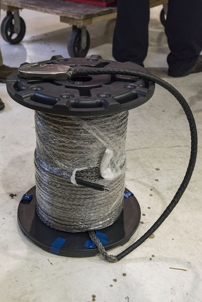 Application engineers from Samson Rope, Ferndale, Wash., brought the proposed synthetic winch cable for C-17 Globemaster III maintainers to wind on a winch assembly, Jan. 30, 2018, at Dover Air Force Base, Del. The 280-foot synthetic winch cable weighs 14 pounds and is 83 percent lighter than the current 80 pound steel wire cable. (U.S. Air Force photo by Roland Balik)