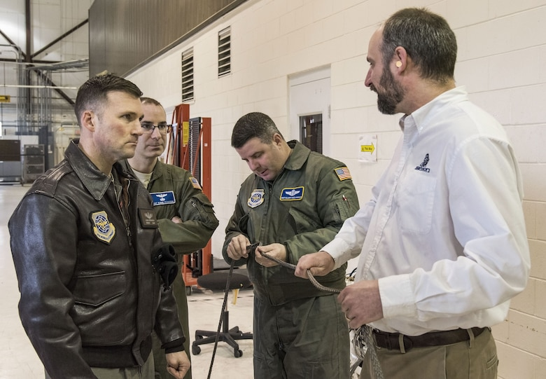 Senior Master Sgt. Jeff Witherly, Headquarters, Air Mobility Command C-17 evaluator loadmaster, Scott AFB, Ill.; Master Sgts. David Feaster and Elliott McClanahan, both 3rd Airlift Squadron loadmasters; listen to Justin Smoak, Samson Rope application engineering manager, Ferndale, Wash., talk about the construction of the winch cable Jan. 30, 2018 at Dover Air Force Base, Del. The 280-foot long steel cable currently used on C-17 Globemaster III aircraft winches weigh 80 pounds versus the proposed synthetic winch cable only weighing 14 pounds. (U.S. Air Force photo by Roland Balik)