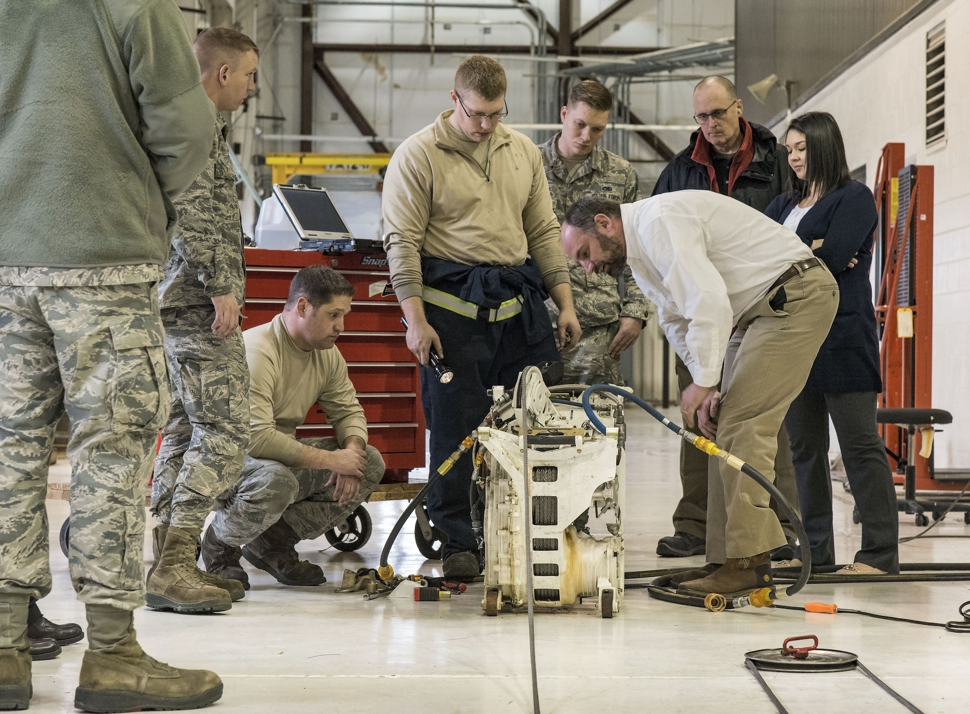 Justin Smoak, Samson Rope application engineering manager, Ferndale, Wash., observes how the synthetic winch line feeds into a C-17 Globemaster III winch assembly, Jan. 30, 2018 at Dover Air Force Base, Del. Smoak watched maintainers attach and wind the cable onto the winch while looking for any potential issues. (U.S. Air Force photo by Roland Balik)