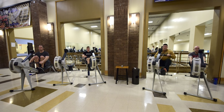Participants of the first Base vs. Base Rowing Challenge begin rowing during the competition opening ceremony at Whiteman Air Force Base, Mo., Feb. 1, 2018. Before getting on one of the designated air rowers, participants check in with the fitness center front desk to ensure their meters are tracked.