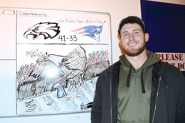 Kody Kolke, a hazardous material handler with the 565th Aircraft Maintenance Squadron, takes a few minutes out of his work day to help boost morale by drawing funny or patriotic scenes on a whiteboard in a heavily-travelled hallway in Bldg. 2121.