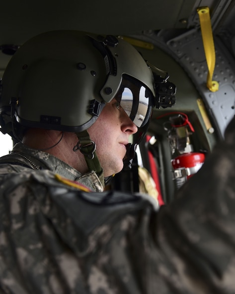 A U.S. Army crew chief with the 1-135th Assault Helicopter Battalion looks out a window of a UH-60 Black Hawk during a joint training mission at Whiteman Air Force Base, Mo., Jan. 31, 2018. In addition to establishing a partnership, the purpose of the training was to familiarize Joint Terminal Attack Controllers from the 7th Air Support Operations Squadron, located in Fort Bliss, Texas, with the assets available at Whiteman AFB that are used in a multi-domain fight. (U.S. Air Force photo by Staff Sgt. Danielle Quilla)