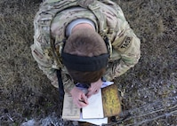 A Joint Terminal Attack Controller from the 7th Air Support Operations Squadron, located in Fort Bliss, Texas, writes down information during a joint training at Warshaw, Mo., Jan. 31, 2018. JTACs are personnel who are authorized to call airstrikes and help coordinate close-air-support missions. (U.S. Air Force by Staff Sgt. Danielle Quilla)