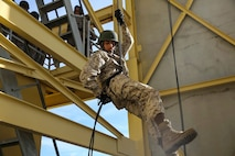 "A recruit of Kilo Company, 3rd Recruit Training Battalion, descends a rappel tower at Marine Corps Recruit Depot San Diego, Feb. 2. One of the techniques learned was how to apply a ""brake hand,"" which is used to adjust the speed while descending the tower. The recruits were given gloves to protect their hands as well as to serve as an extra grip on the rope and a helmet and harness were worn for safety. Annually, more than 17,000 males recruited from the Western Recruiting Region are trained at MCRD San Diego. Kilo Company is scheduled to graduate March 16.