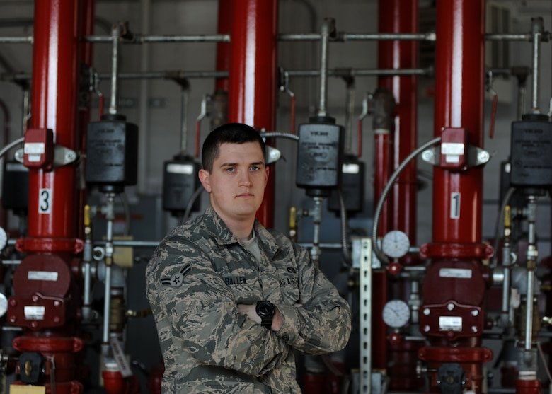 A male is pictured in front of a line of red pipes indoors.