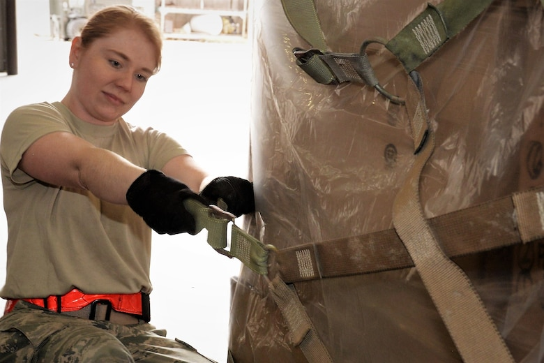 Staff Sgt. Jennifer Shippy, 21st Logistics Readiness Squadron, secures a cargo net around boxes of donated winter weather gear inside the 39th Aerial Port Squadron's loading bay at Peterson Air Force Base, Colorado, Jan. 29, 2018. The winter clothes, donated by Cyrus International, Inc., are being transported via a C-17 Globemaster aircraft from March AFB, California, to mountainous villages in Afghanistan. (U.S. Air Force photo by Staff Sgt. Frank Casciotta)