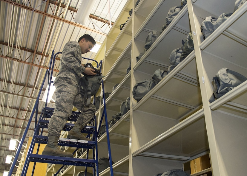 Airman 1st Class Christian Escobedo, an individual protective equipment journeyman assigned to the 97th Logistics Readiness Squadron, grabs a gas mask pouch from the top of a rolling storage unit Feb. 09, 2018, at Altus Air Force Base, Okla.