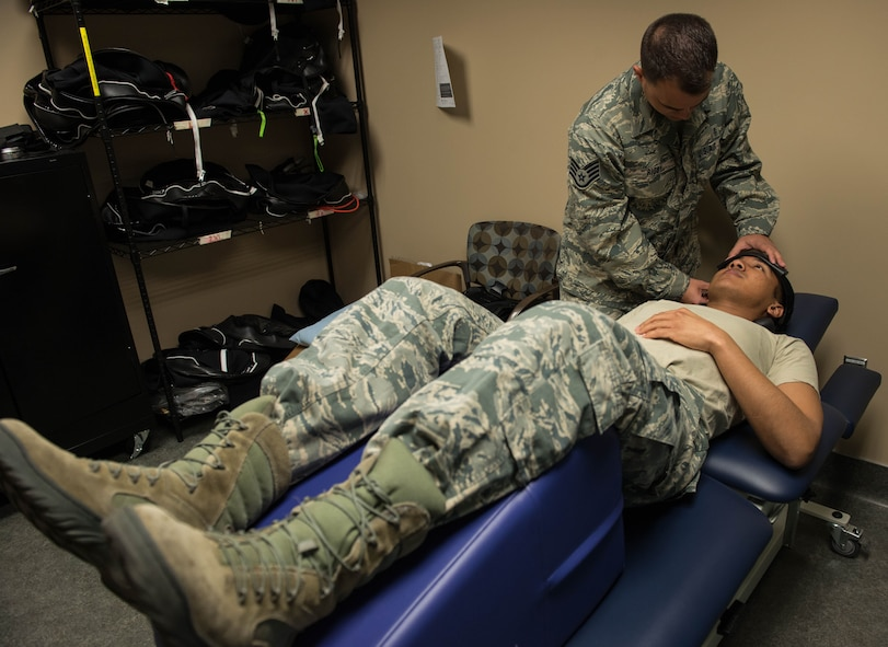 Staff Sgt. Geoffrey Rigby, 56th Medical Operations Squadron physical therapy technician, demonstrates physical therapy techniques on another physical therapy tech, Senior Airman Omar Irvin, at Luke Air Force Base, Feb. 6, 2018. Rigby used his physical therapy knowledge to help save a life after a car crash Jan. 16 in Glendale, Ariz. (U.S. Air Force photo/Airman 1st Class Alexander Cook)