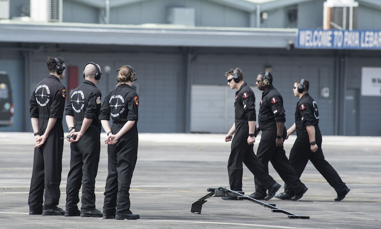 U.S. Air Force Airmen with the Pacific Air Forces' F-16 Demonstration Team march to their finishing position prior to a practice at Paya Lebar Air Base, Singapore, Feb. 3, 2018.