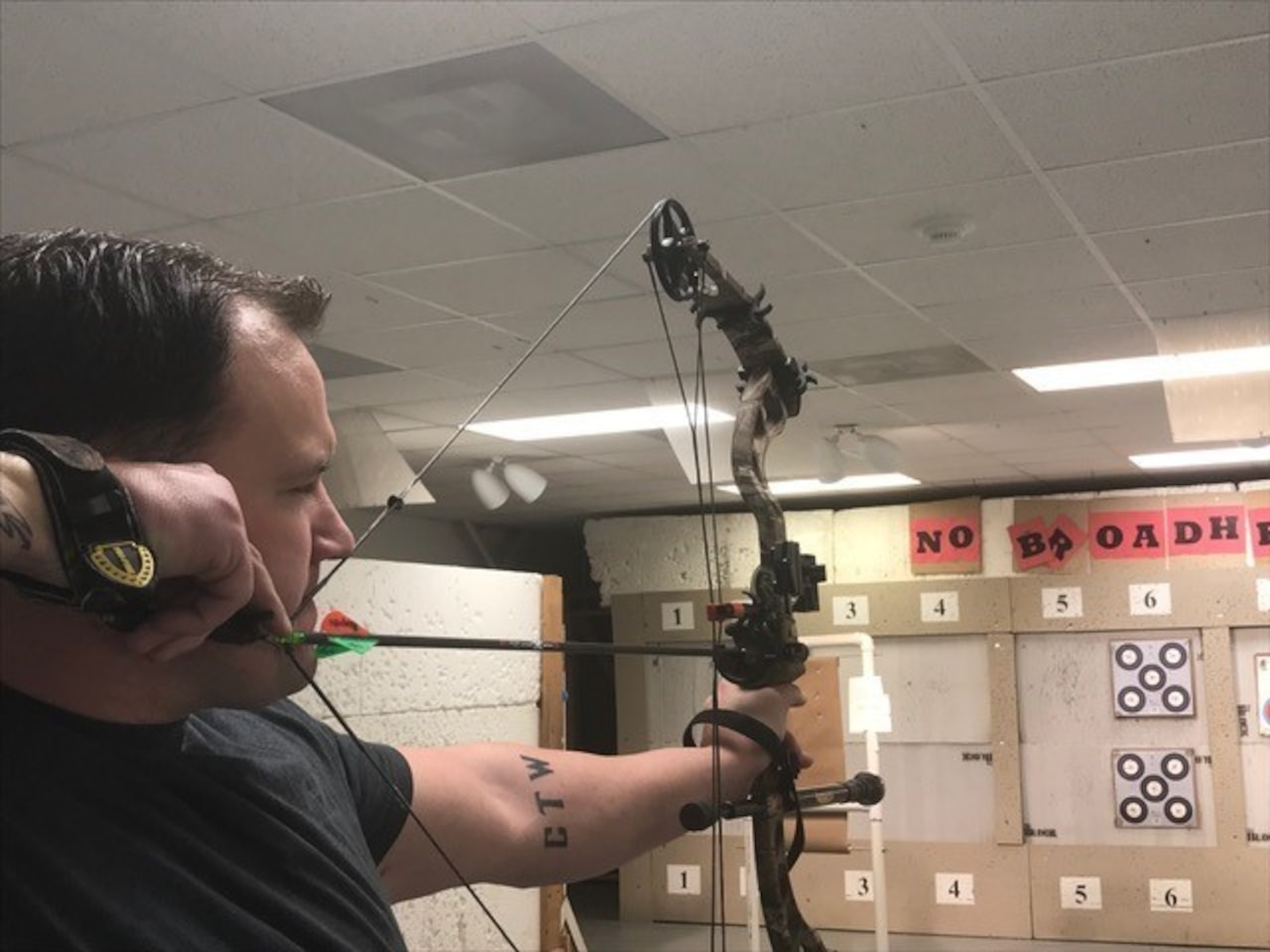 Soldier draws his bow while training for archery competition.