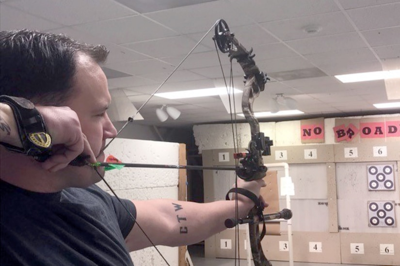 A person draws a bow and aims at a target indoors.