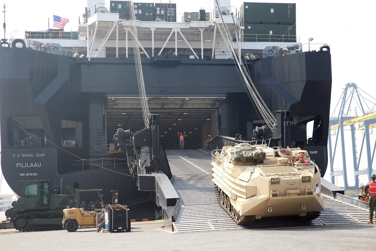 Heavy equipment rolls off the ramp of a U.S. cargo ship in Thailand.