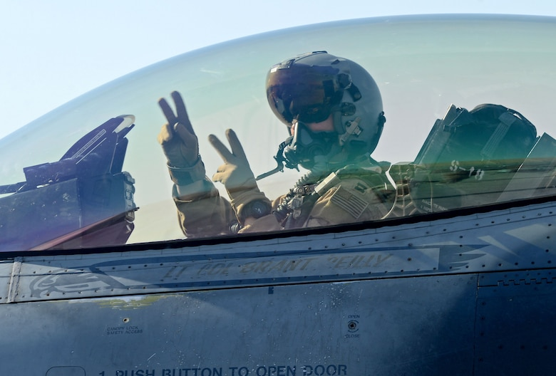 """Slapshot"", 77th Expeditionary Fighter Squadron F-16 Fighting Falcon fighter pilot, signals from his aircraft prior to taking off Feb. 9, 2018 at Bagram Airfield, Afghanistan."