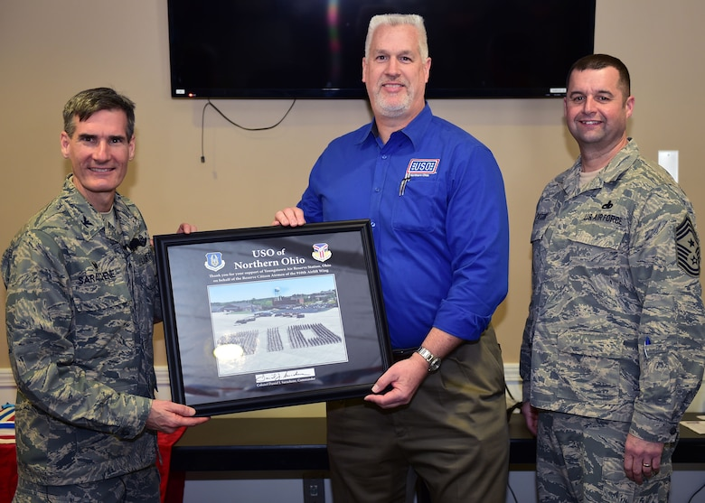 Col. Dan Sarachene, commander of the 910th Airlift Wing, and Chief Master Sgt. Robert Potts, Command Chief of the 910th Airlift Wing, present a Wing photograph to Bruce Bille, executive director of the USO of Northern Ohio, Feb. 11, 2018.