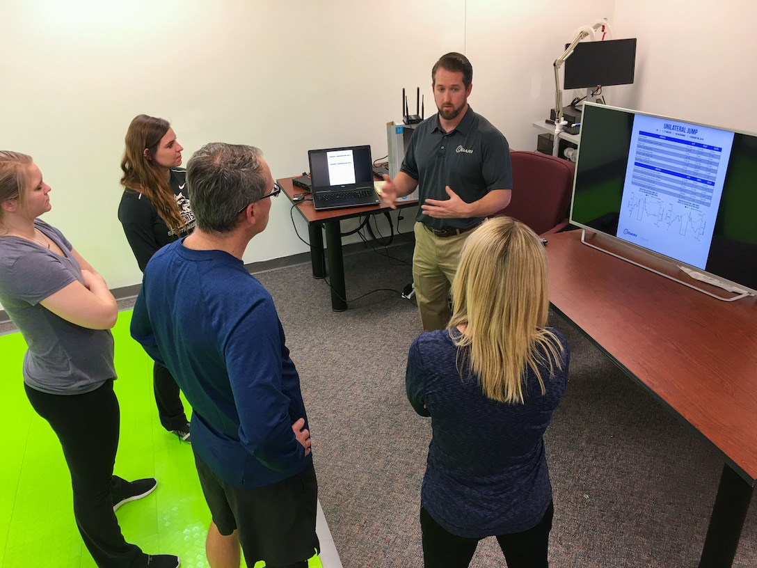 Mike Prewitt, Scientific Analytics DARImotion clinical manager, goes over a report generated by the Dynamic Athletic Research Institute 3D biomarkerless system with research physiologists and contract research athletic trainers from the United States Air Force School of Aerospace Medicine. The DARI system looks at how a person is able to move their body while performing functional tasks and can predict where an injury might occur up to two weeks before it might happen. (U.S. Air Force photo/John Harrington)