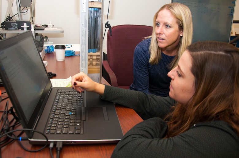 Molly Wade (top), a research physiologist at the United States Air Force School of Aerospace Medicine, and Ashley Kesler, a USAFSAM contract research athletic trainer, go over some of the operations of the Dynamic Athletic Research Institute 3D biomakerless system before conducting a practice assessment. Wright-Patterson Air Force Base is the only base in the Department of Defense researching the many capabilities of the DARI system along with assessing Airmen who may be prone to musculoskeletal injury. (U.S. Air Force photo/John Harrington)