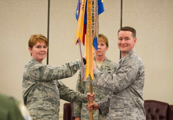 Col. Cherie Roff, 315th Mission Support Squadron commander, passes the 38th Aerial Port Squadron guide on to Maj. Jason Scnyder, new 38th APS commander, during a 315th MSG double assumption of command ceremony Feb. 11 at Joint Base Charleston, S.C. Snyder previously served as the 38th APS operations officer. (U.S. Air Force photo by 1st Lt. Rashard Coaxum)