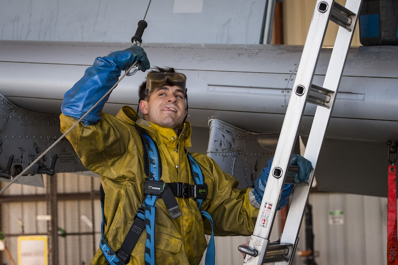 Airman 1st Class Jake Dromgold, 74th Aircraft Maintenance Unit crew chief, prepares to connect his harness to a hook, Feb. 8, 2018, at Moody Air Force Base, Ga. In addition to mechanical and electrical maintenance, A-10's must be washed every 180 days or approximately 1,000 flying hours in order to control corrosion caused by residue from the gun and engine exhaust. (U.S. Air Force photo by Senior Airman Janiqua P. Robinson)