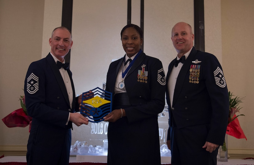 Chief Master Sgt. Larry C. Williams, U.S. Air Force Expeditionary Center command chief, left, recognizes Senior Master Sgt. Carol Dorman-Gore, 628th Force Support Squadron superintendent, center, along with Chief Master Sgt. Todd Cole, 628th Air Base Wing command chief, right, during the chief master sergeant recognition ceremony at the Charleston Club Feb. 10, 2018.